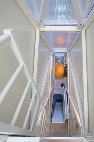 Na sala de estar da Casa Keret, em Varsóvia, Polônia, à frente, o alcapão que leva ao andar inferior e ao fundo, o grande pufe na cor alaranjada que se contrasta com as paredes brancas. A estreita residência localizada espremida entre dois prédios foi projetada pelo arquiteto polonês, Jakub Szczesny.