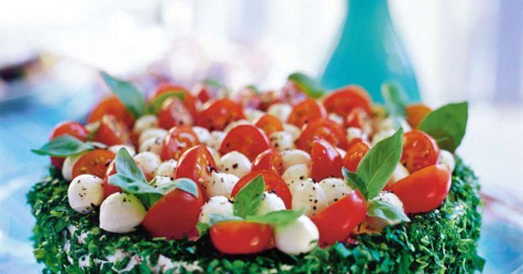 Etsinnässä ihana kasvisvoileipäkakku? Kaunis tomaatti-mozzarellakakku on silmänilo ja juhlapöydän mehevin herkku, jossa maistuvat tomaatti, mozzarella ja basili