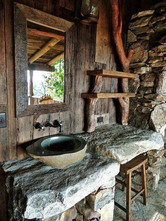 Could you get any more rustic than this bathroom? Slabs of rock, wooden shelves on a tree trunk, and a mirror framed by bark. | Rustic Bathroom Design 12 | #cabin Tiny Homes