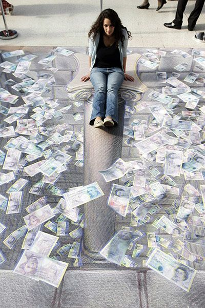Credit: Sang Tan/AP 24 July 2008: A woman poses in Kurt Wenner's 3D illustration of an open vault containing British currency at Waterloo st...