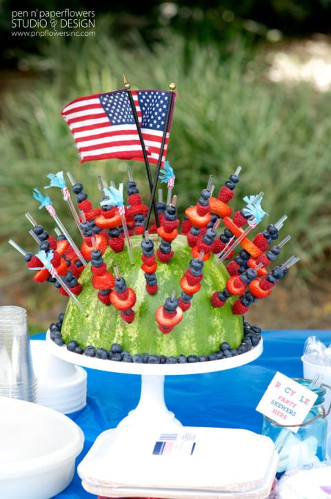 13 Scrumptious 4th of July Appetizers to Kick Off Your Party: FOURTH OF JULY WATERMELON CENTERPIECE: Pop skewers into a halved watermelon for a refreshing snack that doubles as a table topper.  Get the recipe at Pen N' Paper Flowers.