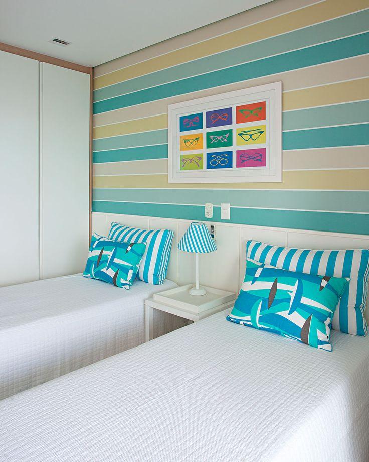 Decoração de apartamento com cores praianas a decoração do quarto de solteiro com papel de parede, quadro colorido e almofadas azuis.