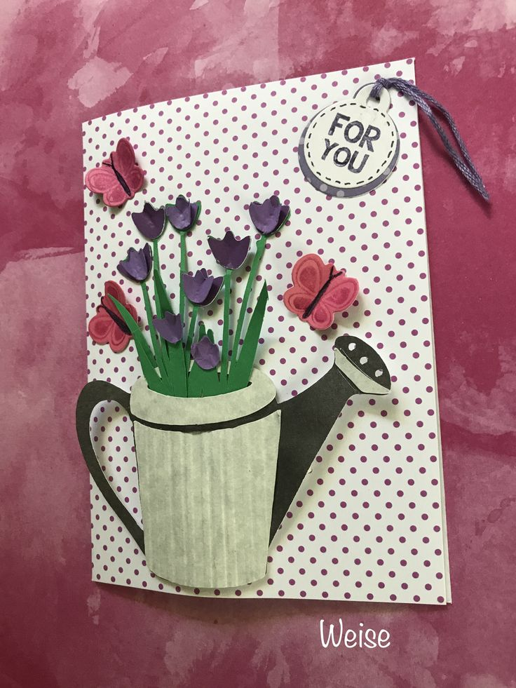 """Walk In My Garden - A2 card base. Tulips, pg 49, were cut @ 2.25"""" using border and border (shift) keys. Cut multiple shift key border flower tops using different shades of the base color, then crease to add dimension and adhere to base tulip flowers. Watering Can, pg 64, was cut at 2.25"""" and main bodyof can was embossed with Paper Studio Stripes embossing folder. Use foam tape on inside edges of can to round out the shape. Add butterflies and sentiment. Created by: Melanie Weise"""