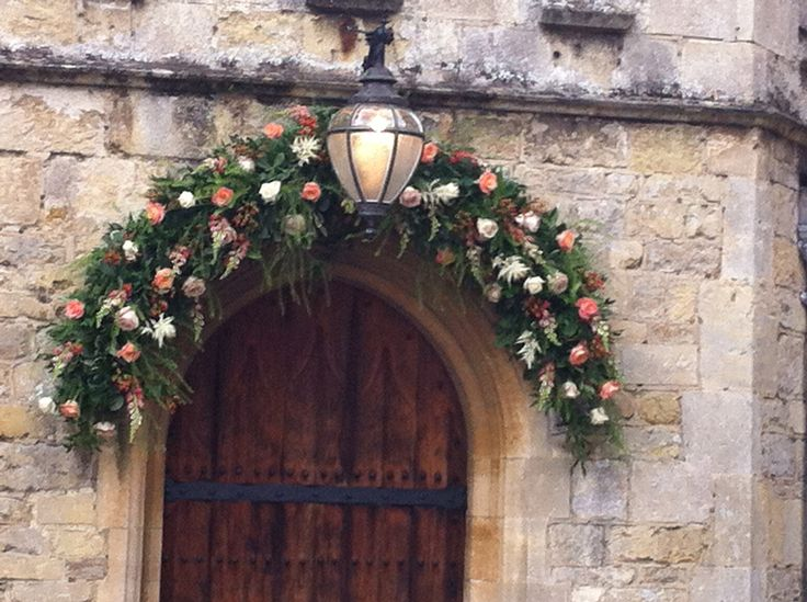 A beautiful ivory, cream and coral archway swag over the front door at Notley Abbey