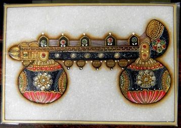 This lovely meenakari kundan painting on a marble tile shows a beautifully made veena- the instrument of Goddess Saraswati.  A unique creation, can be framed for use as wall art. Size: 6 in x 4 in.