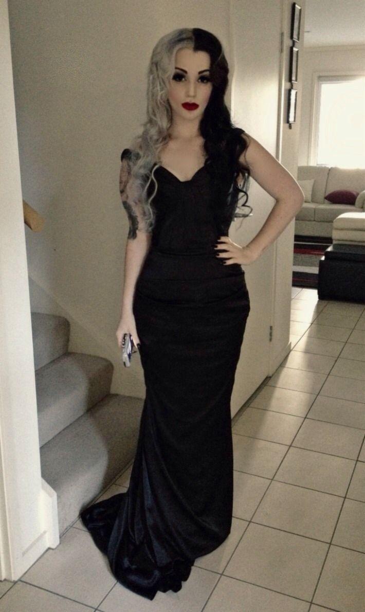 Half black and half white dyed hair. Black maxi formal dress. Very Modern Day Morticia Addams. Nu Goth.