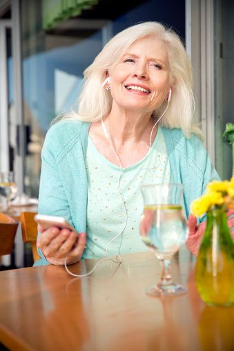 Portrait of senior woman with smartphone hearing music with earphones