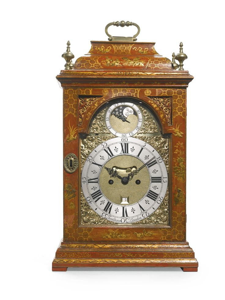 A red japanned table clock, William Tomlinson, London, circa 1740 8-inch dial with female mask and scroll spandrels, signed Tomlinson, London, matted centre with mock pendulum and date apertures, moon dial in the arch, strike/silent lever above XI, the movement with six knopped pillars, verge escapement, striking on a bell and pull quarter repeating on a nest of six bells, the foliate engraved backplate signed Wm Tomlinson, London, the case with inverted bell top, brass carrying handle