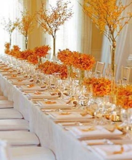 Grand table of spring flowering branches and low tangerine colored arrangements. Excellent way to adorn a super long reception table, especially in a ballroom with high ceilings.