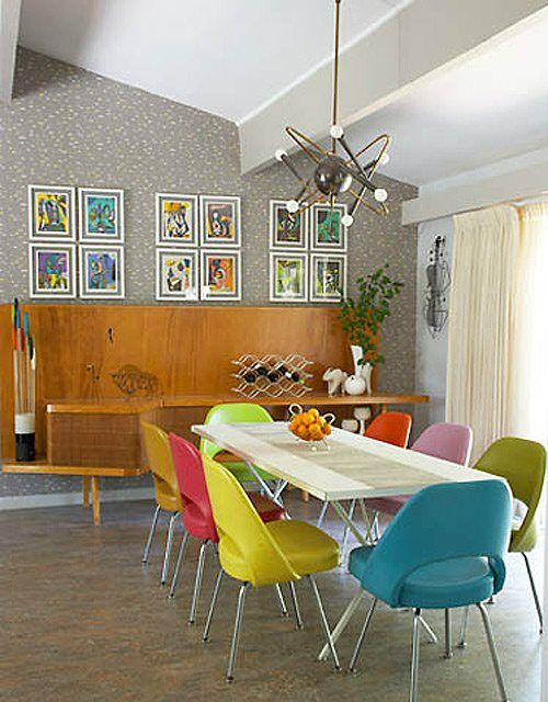 A dining table flanked by mid century modern chairs - Saarinen Executive chairs, to be exact - with a wonderful satellite orbit sputnik lamp above.