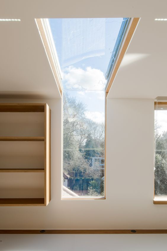 This is a really well thought out loft conversion project. We love the simple folded steel shading device around the dormer windows and how the architect has used matching roof tiles to seamlessly integrate the new addition with the existing roof. The stand-out feature of this design, however, is that window that folds up and over to become a skylight, bringing both a view of the trees beyond and the sky above into the bedroom space.