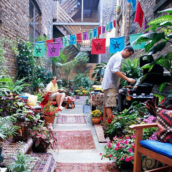 Decorate a Small Courtyard, how festive and cute is this? I like the mitch match rugs with the colorful plants.