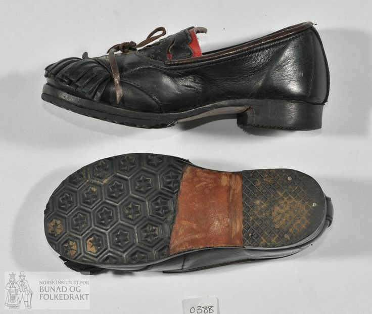 Håndsydde sko i mørke brunt lær til barn. Utskorne applikasjonar montert på raudt lær. Snøring med maljer og frynser. Pålimt gummi under såle og hæl.