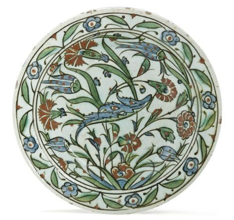 AN INTACT IZNIK POTTERY DISH OTTOMAN TURKEY, CIRCA 1620 On short flat foot, with sloping rim, the decoration on white ground with carnations and tulips, a saz leaf across the center, the rim with palmettes and five-petalled rosettes