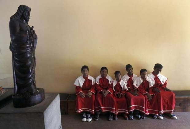 Altar boys sit next to a statue of Jesus Christ while they wait for a Good Friday mass to begin, at a church in Colombo April 18, 2014. (DIN...