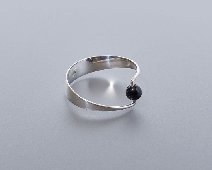 A rare and work by Danish designer Bent Gabrielsen, executed by the Hans Hansen firm in Kolding, Denmark. The work features a tapered sterling silver band turning inward at either end to support a single onyx ball.    MARKED – HANS HANSEN | 925 S | DENMARK | 244    Materials : Sterlin