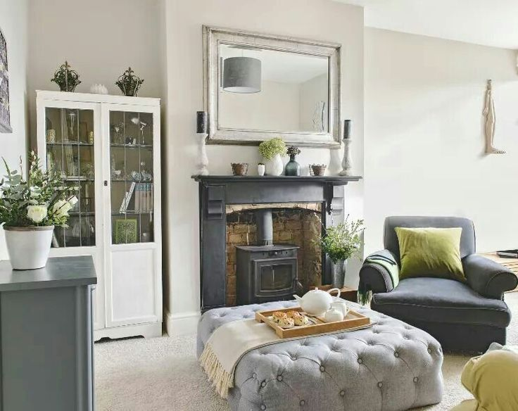 Cozy family room with fireplace, white bookcase, oversized gray upholstered footstool / coffee table