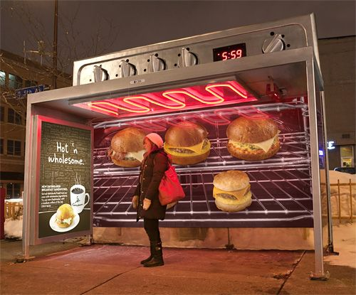"""As part of a campaign for their new """"Hot 'n Wholesome"""" breakfast menu, Caribou Coffee's ad agency, Colle + McVoy, created these amazing bus shelter advertisements for the city of Minneapolis. Not only do they look like giant ovens, but the heating element on the roof actually works! So those waiting inside stay as toasty as the breakfast sandwiches appearing on the poster behind them."""