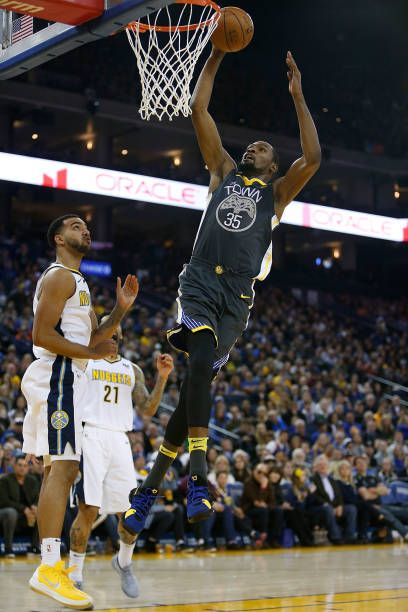 Kevin Durant of the Golden State Warriors dunks the ball against Trey Lyles of the Denver Nuggets at ORACLE Arena on December 23 2017 in Oakland...