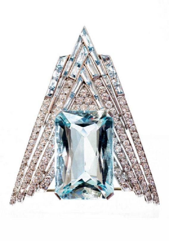 An Art Deco platinum, diamond and aquamarine clip, American, circa 1930. The chevron shaped aquamarine and diamond clip mounted with a central large aquamarine, set with brilliant cut diamonds and French cut aquamarines and mounted in platinum.