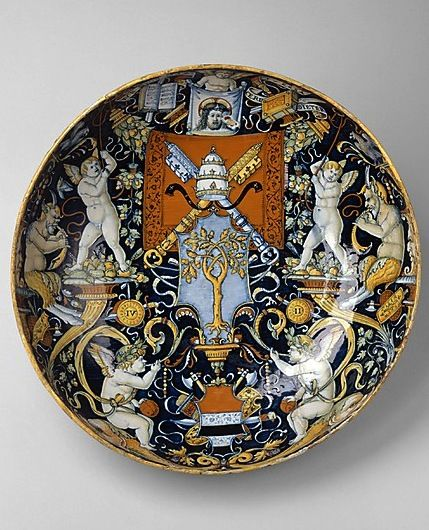"Bowl with the arms of Pope Julius II and the Manzoli of Bologna, maiolica, workshop of Giovanni Maria Vasaro (Italian), 1508 -- The oak tree beneath the papal keys and tiara, the festoons of acorns, and the shields inscribed ""IV II"" (for Julius II) associate this object with Pope Julius II della Rovere (r. 1503–12), whose heraldic device was the oak tree. At the lower edge the coat of arms of Melchiorre di Giorgio Manzoli (Bolognese) who was probably the bowl's recipient."