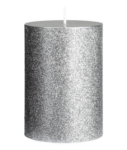 Sølv/Glitrende. Et lite kubbelys i parafin og voks med glitrende overflate. Diameter 7 cm, høyde 10 cm. Brennetid 25 timer.