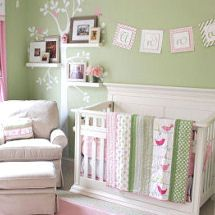 Pink and green baby nursery with tree wall decal and family photos on shelves