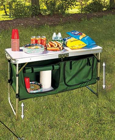 The Portable Camping Kitchen Table lets you prepare and serve food on top and store supplies underneath. Below the foldable table are two large zippered storage sections with fabric-magic straps to tie back the flaps. Use the compartments to store bowls, plates, snacks and more. Table has carrying handles and rubber feet.