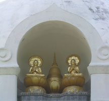 "This is at a Peace Stupa(a peace  pagoda or buddhist shrine). It is that Buddha's cremated remains are divided among local rulers in Northern India. Remains splitted into eight portions. In this  picture of the shrine it shows  2 buddhas on lotus thrones. ""The buddha on the left's hands are in Dharmachakra mudra, the gesture of teaching"""
