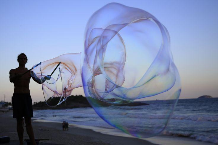 Seniman jalanan Florian Timm membuat gelembung sabun raksasa di pantai Ipanema, Rio de Janeiro, Brazil.