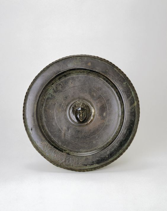 Geek silver plate with medallion of a youth, classical period, 340 B.C.  Allegedly from Galaxidi, near Delphi. It is more like a decorative tondo than an utilitarian vessel, with its border similar to those of mirrors. 22.5 cm diameter. George Ortiz collection