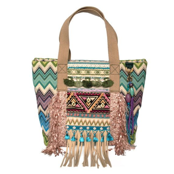 Ibiza tote bag fringed made of turquoise and lilac purple colored fabric. This handmade purse has several pockets inside and closes with two magnetic disks and is lined with a beige cotton. It is made water and dirt resistant. Should it be cleaned, dry cleaning is recommended.  This is really a handmade OOAK item, so dont be too late! Are you looking for a woman gift handmade, youll succeed with this!  Style: Ibiza, hippie, bohemian, boho  Pockets: inside: one for your wallet with zipper, a…