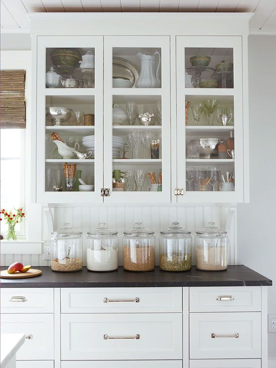 Love this look...white cabinets with glass doors and white drawers (love the drawer pulls, too), dark marble countertop, white beaded-board backsplash.