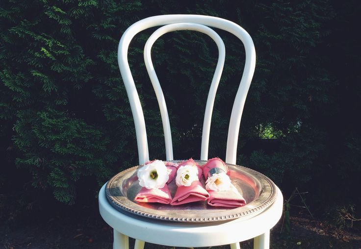 Pink napkins in silver tray. White chair in the garden. DIY ideas. White flowers details.