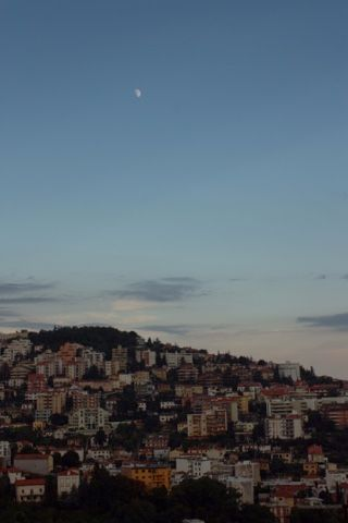 The moon rises during twilight over Trieste, Italy