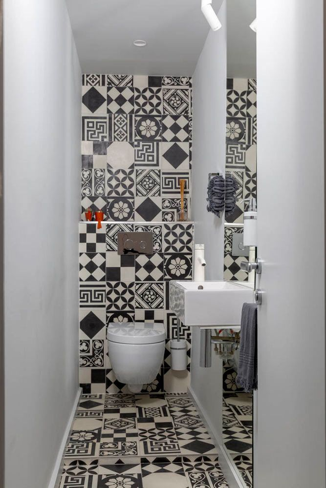 The small powder room features graphic #ceramic tile from Couleurs & Matures #Patchwork. A #Parisian Pied-À-Terre by Piret Johanson Studio #designmilk