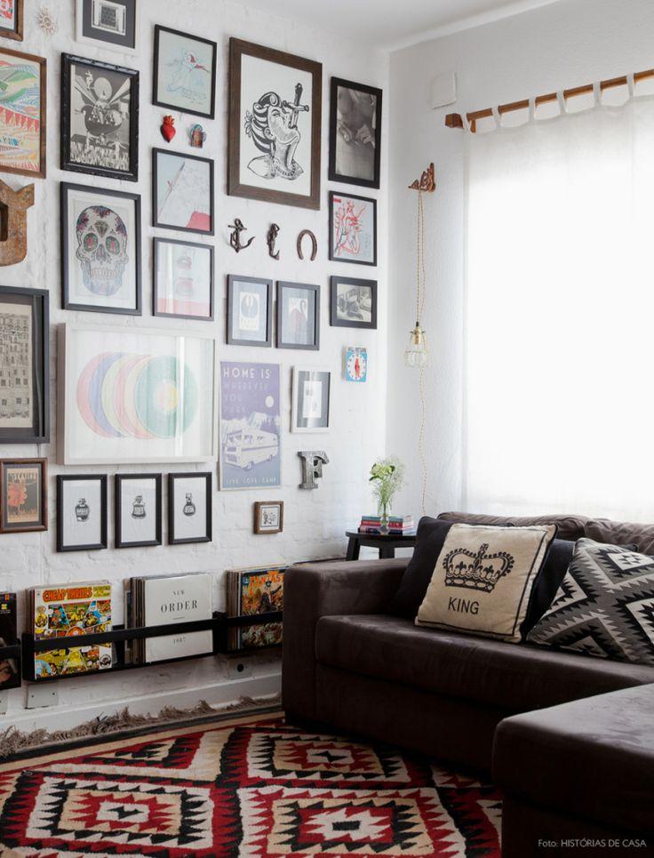 Sala de estar com parede repleta de quadros e objetos de afeto da moradora. O sofá cinza e tapete kilim arrematam o ambiente.