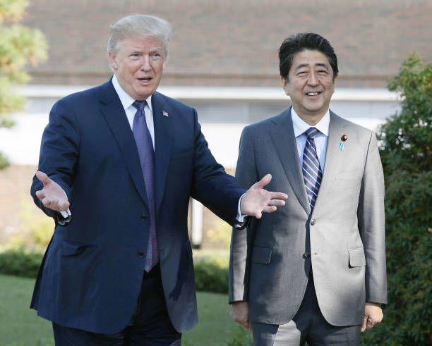 US President Donald Trump gestures beside Japanese Prime Minister Shinzo Abe outside Kasumigaseki Country Club in Kawagoe Saitama Prefecture north of...