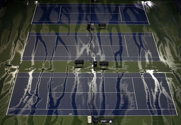 Rainwater streaks across practice courts before Roger Federer, of Switzerland, played Novak Djokovic, of Serbia, in the men's championship match of the U.S. Open tennis tournament on September 13, 2015, in New York.