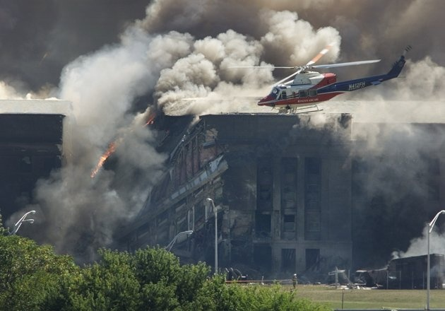 A rescue helicopter surveys damage to the Pentagon as firefighters battle flames after an airplane crashed into the U.S. military Headquarters outside of Washington in an apparent terrorist attack, September 11, 2001.     (REUTERS/Larry Downing LSD/HB)Remember 911, September 11, Photos Gallery, Forget 911, 911Never Forget, 9112001, Photos Photos, 09 11 2001, Power Photos