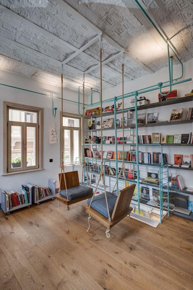 Dans une pièce de style industriel, deux assises-balancelles invitent à la lecture