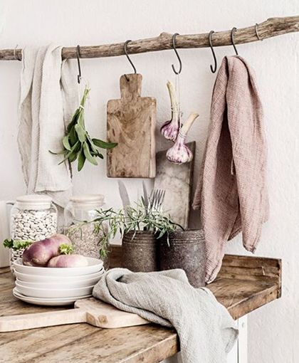 blush pink walls with wooden hanging branch and hooks and pink tea towels and…