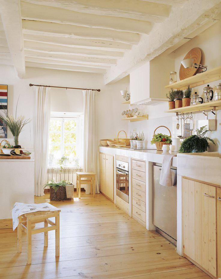 Cocina campestre con muebles de pino y paredes blancas