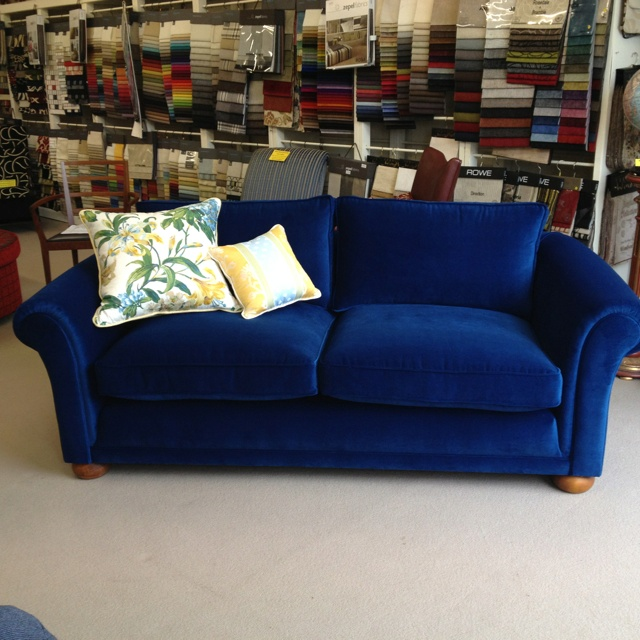 Two and a half seater scrolled arm sofa, with feather cushions and a fully sprung seat.