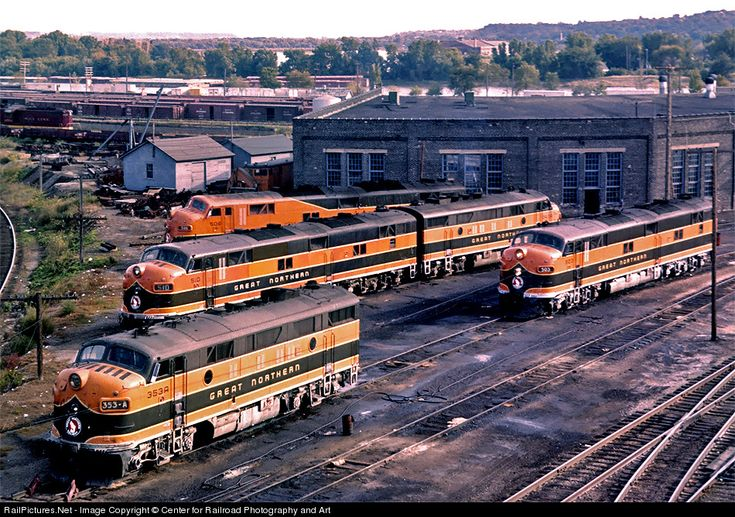 Great Northern Railway passenger power lays over at the roundhouse next to St. Paul Union Depot in the early 1960s. The F3As and E7As pictured here were used on the GN's premier trains, including the Empire Builder, Western Star, and Gopher. The Mississippi River is visible behind the roundhouse, and note the maroon Soo Line geep in the background at far left.
