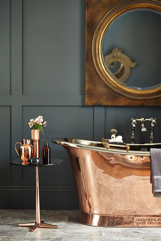 Metal copper bathtub is a luxurious statement piece and compliments the dark paint on the walls.