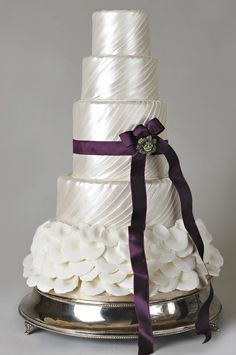 Shimmery Ivory Wedding Cake with Floral Petals, Deep Purple Ribbon & Vintage Jewel Accent