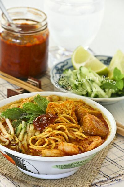 Curry Laksa, a spicy Malaysian coconut based curried noodle soup topped with shredded chicken, shrimps, fried tofu, and bean sprouts.