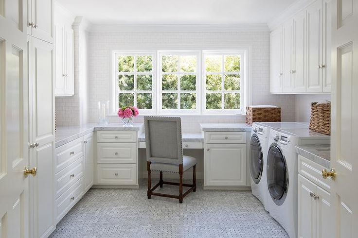 Laundry room and office combo features white cabinets adorned with nickel hardware paired with marble countertops and a white mini subway tiled backsplash.