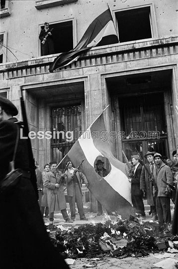 The Hungarian Revolution began with a first mass-rally in Budapest on October 23,1956.It was crushed by Soviet troops after days of street-fighting.The insurgents have unfurled the Hungarian national flag in a window of the Headquarters of AVO,the Communist Secret Police,while in the foreground a flag has been stripped of the Communist symbol, hammer and sickle.